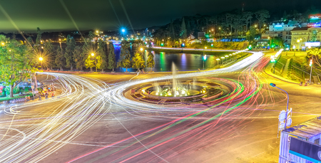 Lam Dong, Vietnam - December 10th, 2014: Roundabout intersections with lights Dalat night market, creating in streaks of color in cars stayed in the city for the evening mist Da Lat, Lam Dong, Vietnam Editorial
