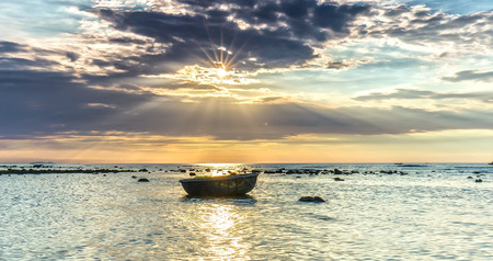Sunset at sea with the projection beam ray Into the sea next to a basket boat Expressed accent is before playing alone with the sea at Ly Son Island, Vietnam Stock Photo