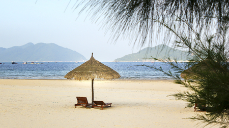 Two lounge chairs with thatched umbrella on beach Expressed desire to waiting couples resort, relaxing beautiful place in Vietnam seas