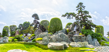 to incorporate: Ho Chi Minh City, Vietnam - March 3rd, 2014: Bonsai garden beauty with many cypress, pine, stone architecture and ancient trees as paintings incorporate blending in Ho Chi Minh City, Vietnam. Stock Photo