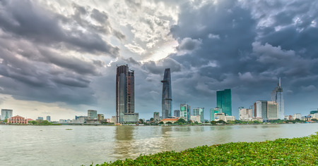 Ho Chi Minh City, Vietnam - July 5, 2015: dynamic city skyscrapers Daylight shone on Saigon river Reflected emblem beside the boat was floating over beauty in Ho Chi Minh City, Vietnam