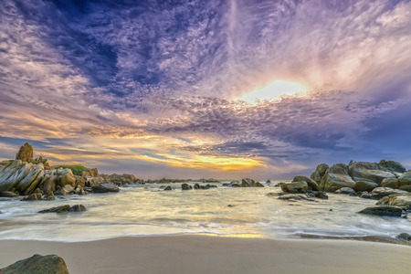 Dawn on the beach with brightly colored clouds, beneath a rock with beautiful scenery create beautiful shapes welcome fresh bright day