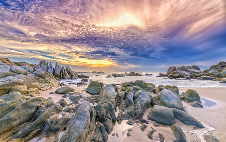 ne: Dawn on the beach with brightly colored clouds, beneath a rock with beautiful scenery create beautiful shapes welcome fresh bright day
