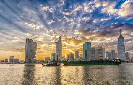 Ho Chi Minh City, Vietnam - February 14th, 2017: Riverside City sunset clouds in the sky at end of day brighter coal sparkling skyscrapers along beautiful river in Ho Chi Minh City, Vietnam Editorial
