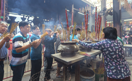 first day: Ho Chi Minh City, Vietnam - January 28th, 2017: Pilgrims pagoda Lunar New Years Day with hundreds of people holding bouquet of incense tingle slave to pray for peace in the temple joyful atmosphere, the first day bustle in Ho Chi Minh City, Vietnam