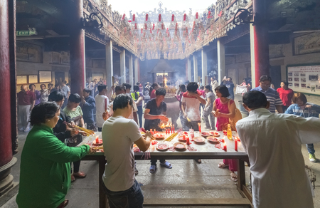 bustle: Ho Chi Minh City, Vietnam - January 28th, 2017: Pilgrims pagoda Lunar New Years Day with hundreds of people holding bouquet of incense tingle slave to pray for peace in the temple joyful atmosphere, the first day bustle in Ho Chi Minh City, Vietnam
