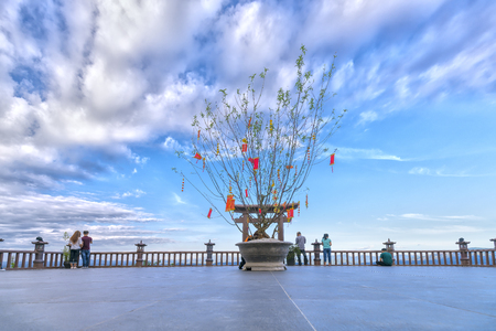 Bao Loc, Vietnam - February 17th, 2017: Temple courtyard Linh Quy Phap An in the afternoon with clouds floating beside the peach tree in blooming peacefully in the land of the Bao Loc, Vietnam.