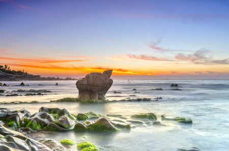 igniting: Dawn on ancient rocks moss covered with colorful sky welcome beautiful new day on the bay Stock Photo