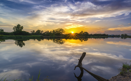 Sunset along the river as the sun down Sunstar really dramatic horizon of a sunny day end. Stock Photo