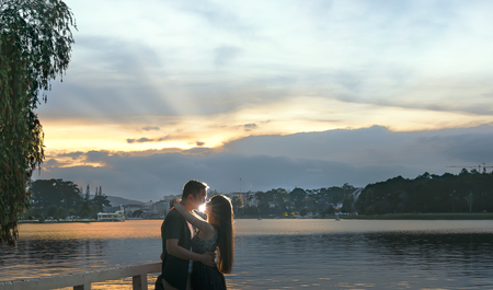 Da Lat, Vietnam - March 27th, 2017: The couple are kissing at sunset to the shores of Lake Xuan Huong. This is a popular tourist attraction to yearly visitors to Da lat, Vietnam