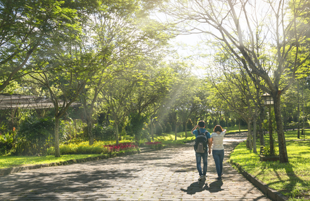 Dong Nai, Vietnam - June 25th, 2017: Happy couple walking together at the end of the road in eco tourism with two rows of green trees adorn the romantic scenery for honeymoon in Dong Nai, Vietnam