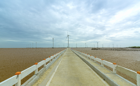 Clean energy, wind power plant with a pathway to the giant wind turbines at the sea to provide electricity for human life. Stock Photo