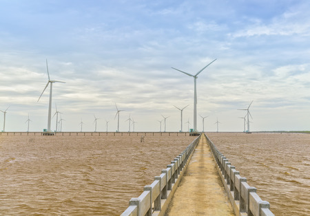 provide: Clean energy, wind power plant with a pathway to the giant wind turbines at the sea to provide electricity for human life. Stock Photo