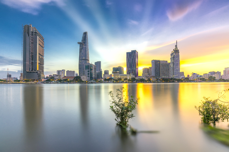 developing country: Ho Chi Minh City, Vietnam - June 15th, 2017: Riverside City sunrays clouds in the sky at the end of the day brighter coal sparkling skyscrapers along the beautiful river in Ho Chi Minh City, Vietnam