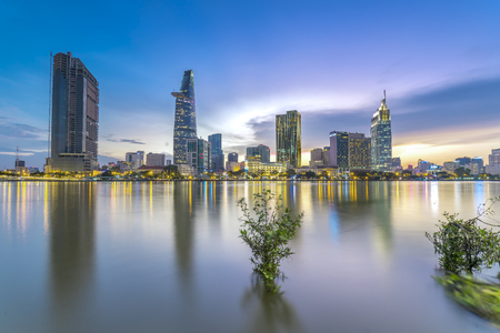 Ho Chi Minh City, Vietnam - June 15th, 2017: Riverside City sunrays clouds in the sky at the end of the day brighter coal sparkling skyscrapers along the beautiful river in Ho Chi Minh City, Vietnam