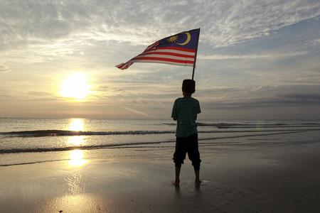独立記念日の概念-日の出の岸にマレーシア国旗を掲げた少年 写真素材