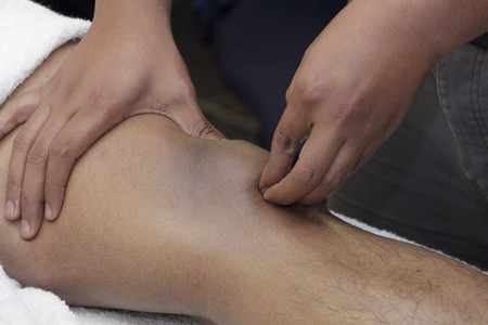 massage homme: massage sportif - les mains des hommes font des massages sportifs de la part du corps humain