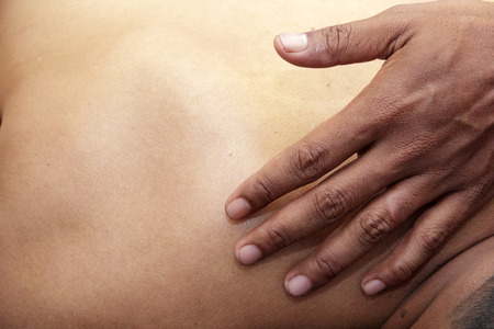back ache: sport massage - mens hands are doing sport massage on the part of the human body