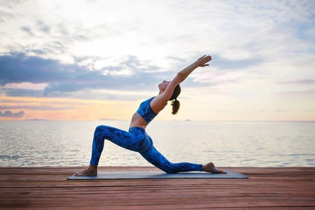 Young woman practicing yoga on the sunset beach Stock Photo - 68312050
