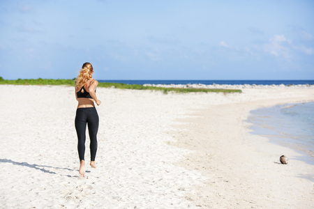 young fitness woman running at beach. stock image.