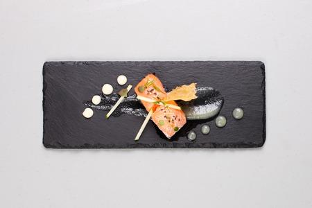 Salmón ahumado con hierbas, fingido huevas de salmón. Salsa preparada por la técnica gastronomía molecular. Foto de archivo - 91382151