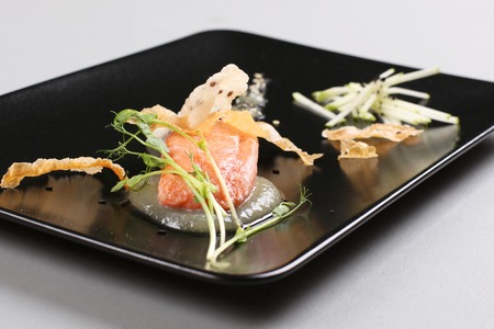 Smoked salmon with herbs, faked salmon roe. Sauce cooked by molecular gastronomy technic. Foto de archivo