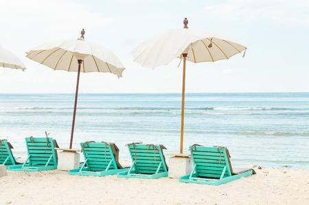 Invitando a sillas con paraguas en una playa cerca del océano. Imagen de archivo. Foto de archivo - 91355895