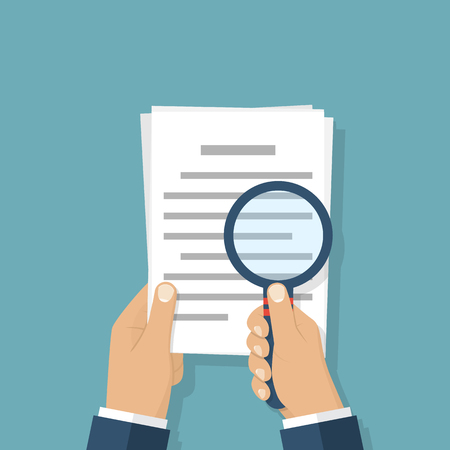 Hand holding magnifier and paper document. Business concept.