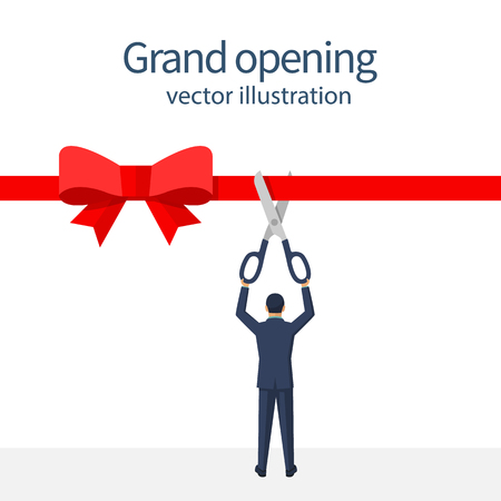 Businessman is holding big scissors cutting red ribbon.