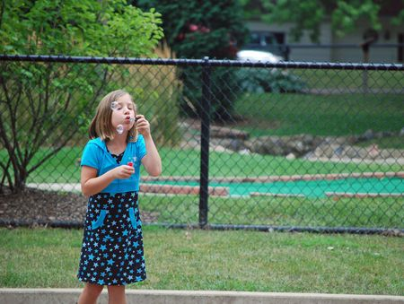 Little girl blowing bubbles at the park Stock Photo