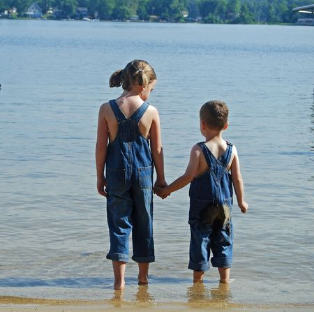 kids holding hands at the beach in overalls