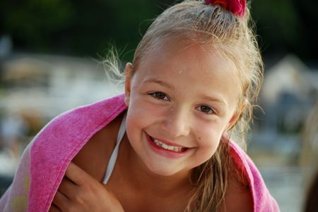 A happy little girl dries off after swimming Stock Photo