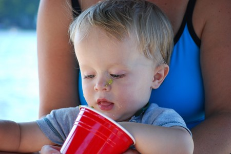 a cute baby eats guacamole from a cup while on his moms lap Stock Photo