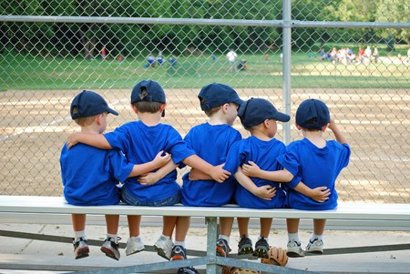 five little boys put their arms around each other while waiting for  their baseball game to start 스톡 콘텐츠