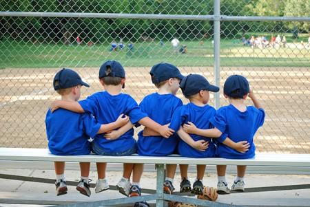 vijf kleine jongens hun armen om elkaar heen in afwachting van hun honkbal spel te starten