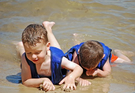 two little boys do their best army crawl on the beach Stock Photo