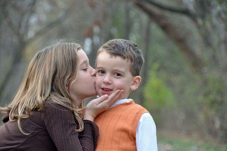 秋の散歩に 2 人の子供のキスします。