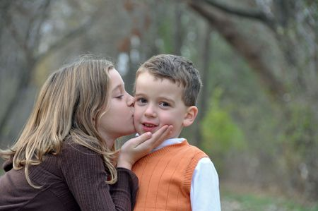 two kids kiss while on a walk in autumn Stock Photo