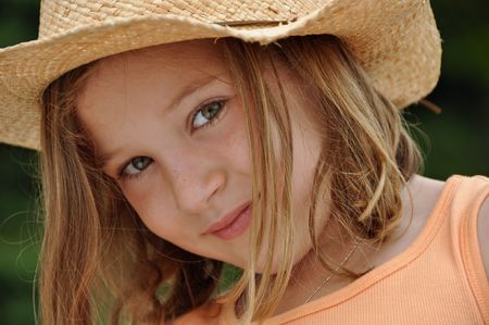 a beautiful little girl wears a cowboy hat