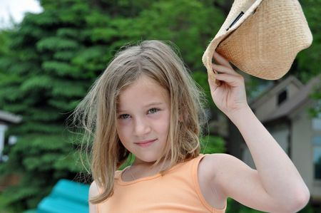 a little girl shows off and raises her cowboy hat Stock Photo - 6353039