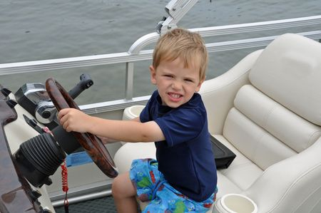 a cute little boy drives a boat