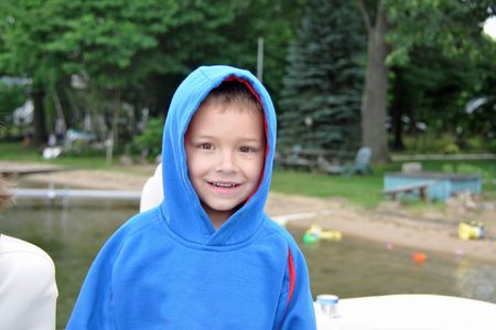 a cute little boy warms up at the lake