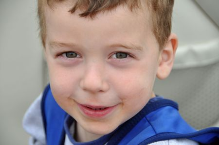 a little boy shows off his messy face while boating