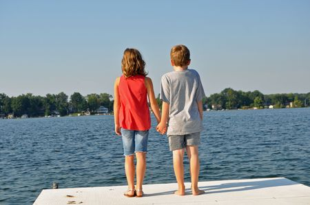 two young children hold hands on the pier Stock Photo