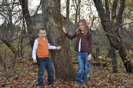 two children enjoy an autumn day in the woods photo