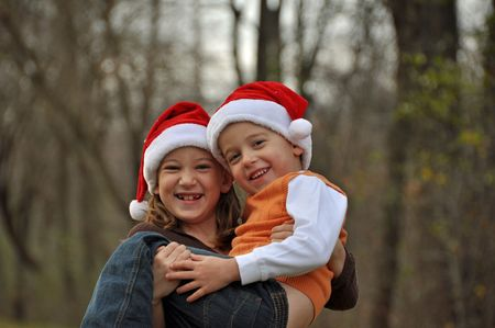 a young girl holds her brother while wearing a santa hats photo