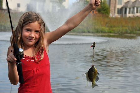 a young girl catches a fish photo