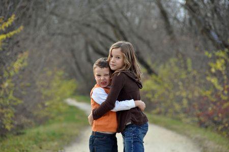 秋の日に不機嫌になる少年と彼の妹を抱擁します。