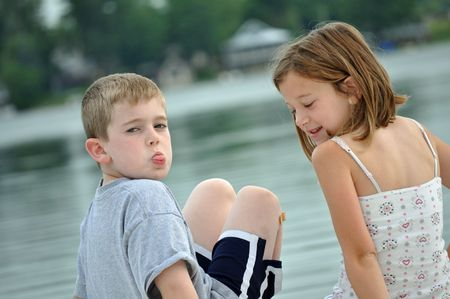 a little boy and girl make funny faces on a summer day at the lake