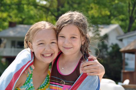 two little girls dry off after swimming Stock Photo